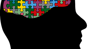 Black image of profile with puzzle pieces coming out of top of head